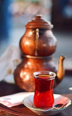 Turkish Tea ..by özgür Bilgin (Turkish tea is served in a tulip shapped glass. It's prepared in a copper teaspot seen at the back ground )
