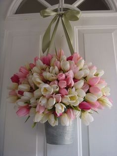 Wreaths don't work for you? Worry not. Just pile a bunch of colourful tulips into an old bucket and string up on the door.