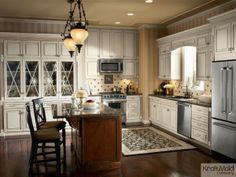 A classic white KraftMaid kitchen featuring a warm island and traditional details.