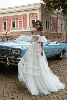 Spectacular boho-style wedding dress with open shoulders and a soft skirt with a train and detachable puffy sleeves. A semi-sheer corset down to the waist is decorated with a plunging cut in the center. The seams are trimmed with a delicate velvet ribbon. Soft, ruffled skirt. The model is decorated with five types of lace.NYC Bride's hand-made-in-Europe wedding dresses, veils and gloves boast the New York City's boldness, expression and style. Beneath the modern design lies the Old World class,
