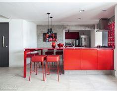 Integrada à sala, a cozinha ganhou mais destaque graças à tonalidade supervibrante da bancada e de sua estrutura metálica.