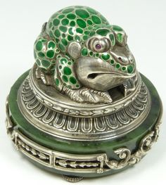 This would be a nice addition to a dressing table:    Imperial Russian silver enameled frog figure having cabochon cut ruby jewels to eyes set on spinach green nephrite jade square base