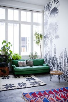 Green sofa and bold patterned rugs in a truly inspiring and creative loft . Photo: Julie Ansiau. Styling Charlotte Huguet. Elle. Copyright reserved.