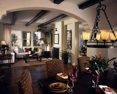 An ornate southwestern style archway leads from the dining room into the living room. The way the exposed beams and hardwood floors flow into the room makes the space feel larger and aesthetically connected.