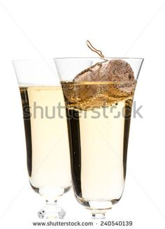 Closeup of two champagne glasses with champagne cork floating in one glass shot on white