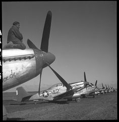"(1945, March) An unidentified Tuskegee airman sitting on top of an airplane, a P-5/D, ""Creamer's Dream"" airplane in the background, Ramitelli, Italy. 
