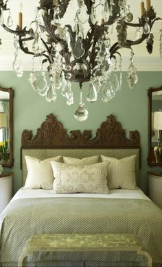 Crisp color with the dark wood headboard and iron and crystal chandelier. Pretty