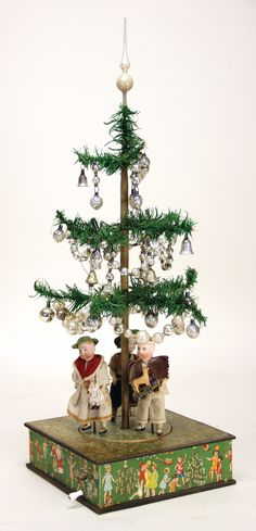 unusual Christmas tree machine, machine with crank with music mechanism, intact, 3 bisque head dolls, mass body, painted eyes, Christmas tree with a height of: 16 cm, depth: 21 cm, width: 21 cm, stuck with lithographed paper