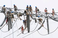 A group of workers climbed onto equipment to perform maintenance work at an electric power station in China's Jiangsu province
