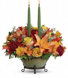 Golden Fall - This glorious centerpiece includes yellow roses, dark orange asiatic lilies, orange alstroemeria, maroon carnations, and brown button spray chrysanthemums. #RAFlorist #Thanksgiving #fallflowers