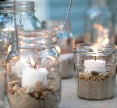 Light up your summer night with beach jar candle holders. A mismatched group of mason jars sits atop a table. Fill your jars with sand, add some mini shells and/or small beach pebbles, place a candle on top, then sit back and enjoy. Glass Jars, Candle Jars, Mason Jar Candle Holders, Mason Jar Crafts, Mason Jars, Beach Jar, Decorated Jars, Beach Crafts, Beach Themes