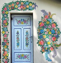Hand painted flowers around a light blue door also hand painted with flowers. I really love this. So pretty!!