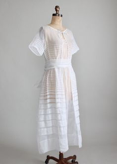 Vintage Early 1920s White Organdy Lawn Dress   - Label  none    - Late 1910s / Late Edwardian / very early 1920s   - The bodice is accented with a small floral cut-out and a bow.  The skirt is lightly gathered at the sides (a subtle Rode de Chine style) with graduated, horizontal pleating.  There is a wide gathered sash around the waist with a large bow in the back.  The dress closes in the front with small snaps.  This would be lovely for a lawn party or even a garden wedding!