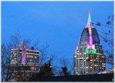 RSA tower in downtown Mobile, Al celebrates Mardi Gras with purple, green and gold lights