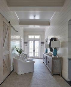 coastal hallway sitting area with shiplap walls and barn door