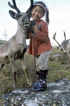 Tsataan Nomads - Dukha (reindeer people) kid holds her favourite reindeer