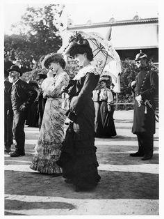 Publik framför kasperteater på Djurgårdsslätten i Stockholm, 25 juni 1905. I förgrunden två unga kvinnor i klänning och hatt, en av dem bär ett parasoll. Till höger i bild står en poliskonstapel i uniform och kask.