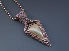 Pointy bronzite cabochon wrapped and woven in bare copper wire. I used twisted wire to frame the stone and to add extra texture. Size: 26mm (1.02in) at its widest point and 62mm (2.44in) in length. Weight: 10.2g. The pendant has had a patina applied to add depth to the copper but is