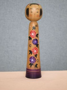 Lovely kokeshi dolls with pink and pruple flowers by Kakizawa Koretaka (a creative take at Naruko style).
