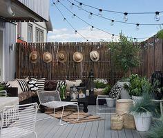 Sichtschutz auf Balkon und Terrasse mit amei Blumentöpfe, HAY Gartensessel, conmoto Outdoor Couch, Windlichter, Lichterketten und vielen Kissen verschönert