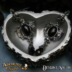 Alchemy Gothic E351 Seraph Of Darkness Stud Earrings (pair)  A pair of classically styled pewter earrings; an angel-winged cartouche bearing a 14x10mm black oval cabochon and a matching crystal dropper suspended from a floriate stud, with surgical steel posts and plastic scrolls.
