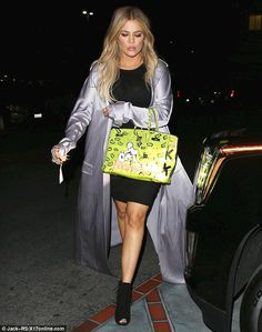 Must-have accessory: Khloe, 30, held on tight to her newest precious Birkin bag painted by graffiti artist Alec Monopoly