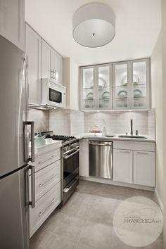Modern kitchen design with white drum flush-mount pendant, white Ikea kitchen cabinets, white quartz countertops, gray glass subway tiles backsplash and gray porcelain tiles floor.