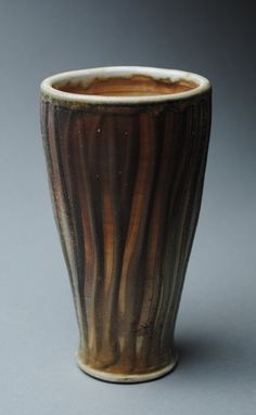 Clay cup handmade and fired in a wood burning kiln. This tumbler sits on a narrow foot and flares out on top. It has beautiful color and