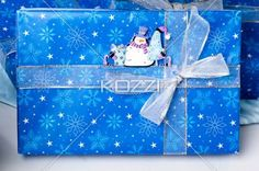 view of christmas box with shiny ribbon and snowman sticker. - Close-up shot of blue Christmas box with shiny ribbon and snowman sticker.