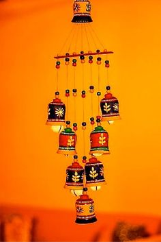 A 'V' shaped arrangement of sevev multicoloured hand painted bells, with a single bell on top, put together with colourful beads, serves as a decorative wind chime. The terracotta pieces have been painted in acrylic colours and thus are water resistant. The product is a creation of local artisans of Delhi.