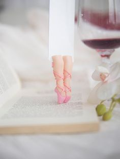 Ballerina bookmark. Tender pink book marker in pointe shoes. Legs in the book.