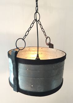 Our one-of-a-kind leather and aluminum pendant lamp adds a touch of rustic to any environment. We've paired a salvaged air conditioning duct with vintage equestrian leather and hardware details. The s