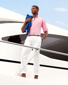 Shop this look on Lookastic: https://lookastic.com/men/looks/crew-neck-sweater-long-sleeve-shirt-chinos-belt-bracelet/11393 — Blue Crew-neck Sweater — White Chinos — Orange Bracelet — Black Woven Leather Belt — Pink Long Sleeve Shirt