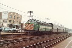 A 1953 vintage EMD E-9 cab unit passenger diesel, is seen stopping at the La Grange Road commuter rail station in downtown La Grange Illinois. These veteran cab unit diesels were in their final years of service, and were officially retired in September of 1992. This is on todays Metra / BNSF Railway 3 track mainline to Aurora Illinois.