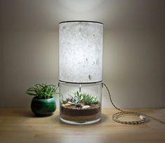 A designer Stephanie Hare da SHare Studios reimaginou as luminárias de mesa, inserindo vasinhos de vidro na base. O pequeno terrário é uma peça de decoraçã
