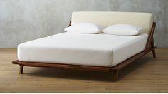 A sleek and modern CB2 wood bed frame.