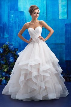 9408  The sheer ruffles adorning this gown's ballgown skirt are both fluid and structured, topped with a floral belt.