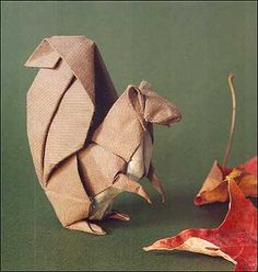 Origami squirrel folded from a single 15 inch square of handmade paper, no cuts. The paper is all brown on one side and all white on the other so two colors show. This piece was part of an exhibit at the Louvre, Paris, in 1998.