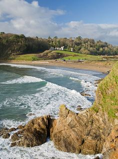 Porthluney Cove / Caerhays Beach in Cornwall, England. Overlooking the beach is Caerhays Castle