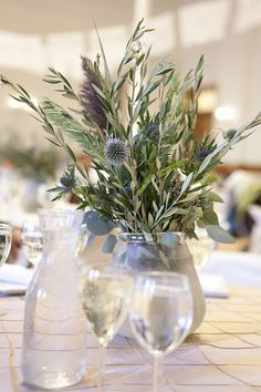 olive branches, thistle, wheat (I would want those spiky blue flowers and hints of more colorful flowers, plus a white vase instead)