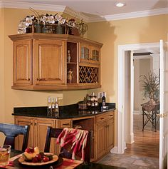 A quiet corner can be transformed into a center for entertaining. Kingston doors by Decora in a warm Coriander Coffee finish convey a traditional welcome.