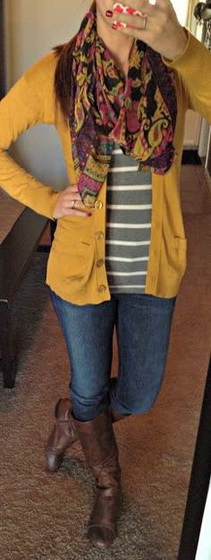Gray and white striped top, black design scarf, dark yellow cardigan, skinny jeans, tall dark brown boots.