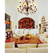 As in other areas, the living room is a repository for art, such as the boldly hued painting by Alejandro Colunga. Contemporary-style sofas wear white slipcovers.