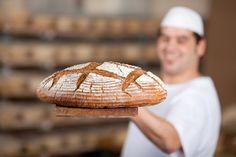 bäcker hält großen brotlaib