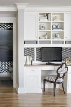 Lovely kitchen features a built-in desk with wood top under inset black and white geometric pin ...