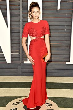 Nina Dobrev partied it up in a red-hot Reem Acra dress with short sleeves, lace appliqués, and cutouts on each side. A gold clutch and a bouffant hairdo completed the look.