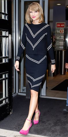 Taylor Swift paid a visit to London's BBC Radio 2 in a perforated chevron-print black knit and a matching pencil skirt, adding a dash of color with bubblegum pink ankle-strap pumps.