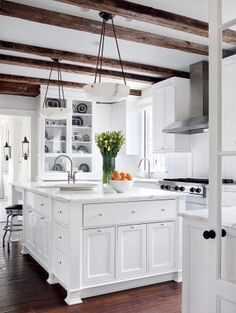 I am in love with the ceiling and beautiful wood beams in this lovely white kitchen...