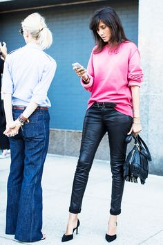 Pink crew neck sweater tucked into black leather pants and black point-toe pumps