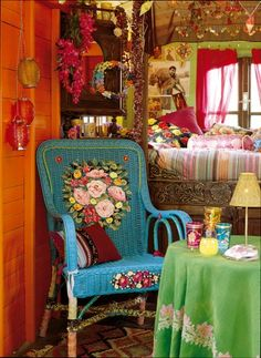 A traditional wicker chair... It is first covered with acrylic paint in a beautiful turquoise blue. Then roses, and cut flowers from different colored fabrics are glued to the back, and embellished with paint if necessary. The legs are wrapped in various pieces of torn fabric.